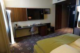 Hotelzimmer mit Schreibtisch, Fernsehrückwand, Garderobe und Kofferstation